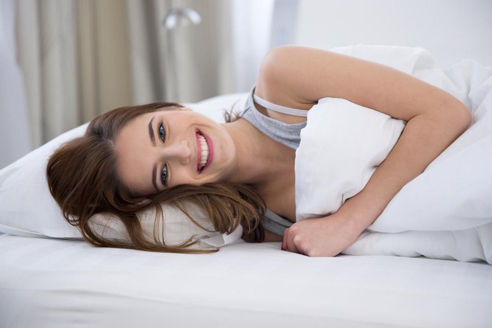 Mulher deitada no colchão abraçada com o travesseiro